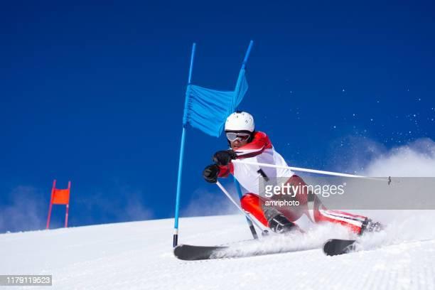 skieur professionnel dynamique pendant la course de ski de super g - événement sportif d'hiver photos et images de collection