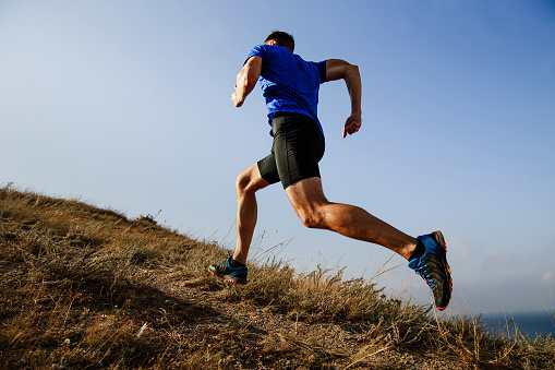 dynamic running uphill on trail male athlete runner side view 862317986