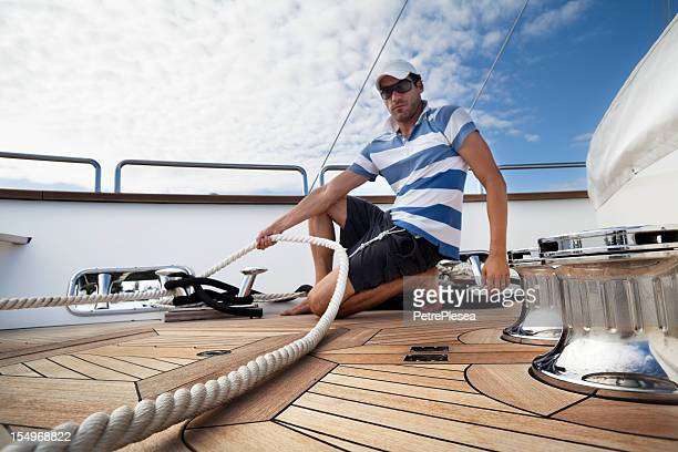 dynamic sailor of the yacht tightening ropes on bollards - tighten stock photos and pictures