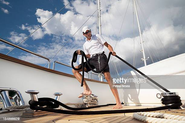 Dynamic sailor on board of the yacht maneuvering with ropes