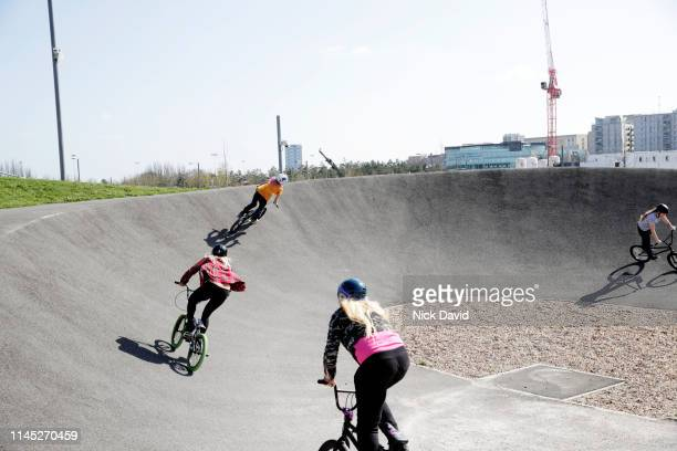 dynamic shot of female bmx cyclists on steep curve on race track - bmx track london stock pictures, royalty-free photos & images