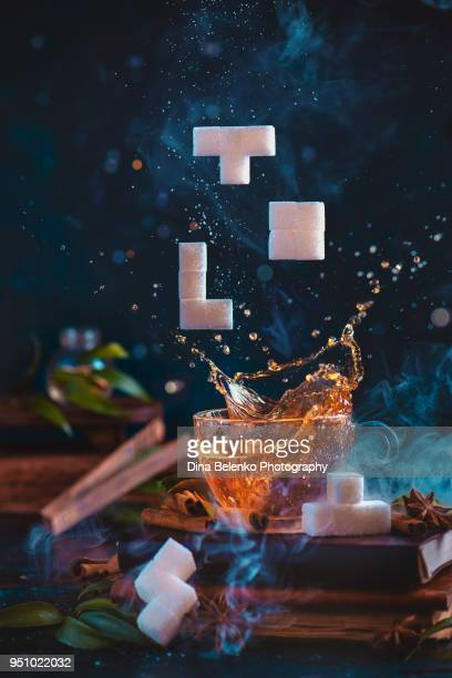 Dynamic tea splash in a glass cup with sugar Tetris pieces. 8-bit video game in real life concept with copy space. Creative action food photography.