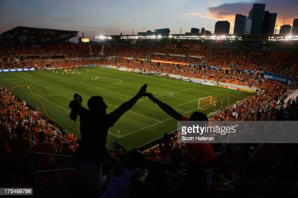 Dynamo fans celebrate after Brad Davis of the Houston Dynamo scored a first half goal against the Columbus Crew at BBVA Compass Stadium on August 3...