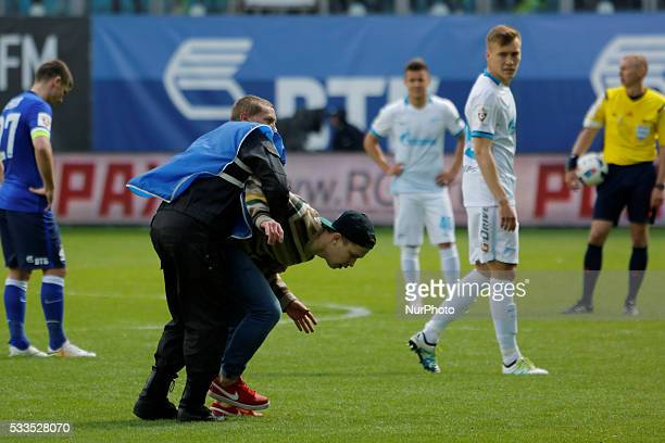 FC Dynamo Moscow supporter is being detained after he ran off onto the pitch during the Russian Football Premier League match between FC Dynamo...