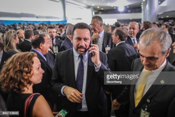Dyogo Oliveira president of Banco Nacional de Desenvolvimento Economico e Social speaks on a mobile device while exiting from a ceremony for new...