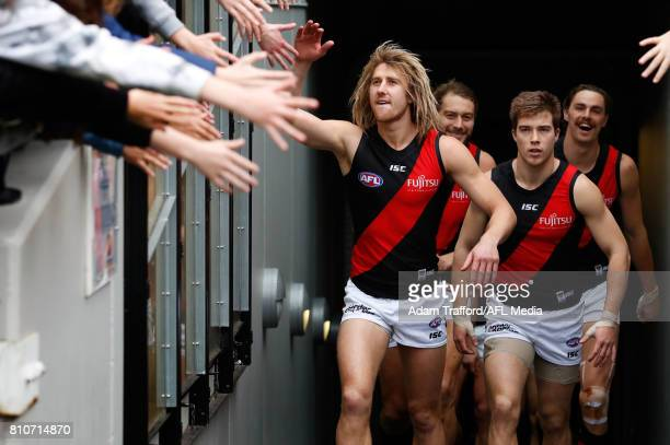 Dyson Heppell and Zach Merrett of the Bombers come up the race during the 2017 AFL round 16 match between the Collingwood Magpies and the Essendon...