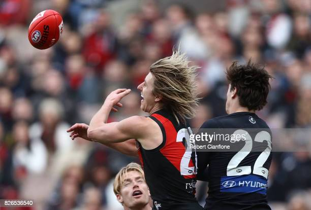 Dyson Heppell of the Bombers and Caleb Marchbank of the Blues compete for the ball during the round 20 AFL match between the Essendon Bombers and the...