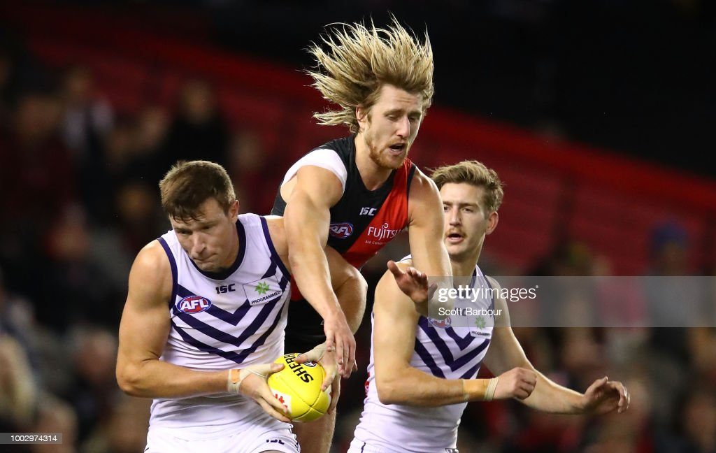 Dyson Heppell of the Bombers and Scott Jones of the Dockers compete for the ball during the round 18 AFL match between the Essendon Bombers and the Fremantle Dockers at Etihad Stadium on July 21, 2018 in Melbourne, Australia.
