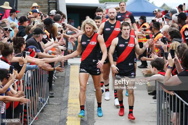 Dyson Heppell of the Bombers and Zach Merrett leads the team out during the JLT Community Series AFL match between the Geelong Cats and the Essendon...