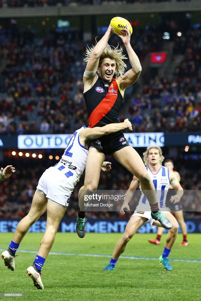 Dyson Heppell of the Bombers gathers the ball from Jy Simkin of the Kangaroos during the round 15 AFL match between the Essendon Bombers and the North Melbourne Kangaroos at Etihad Stadium on July 1, 2018 in Melbourne, Australia.