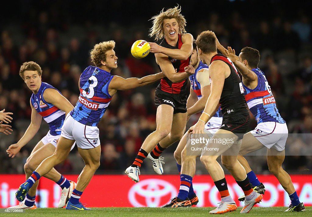 Dyson Heppell of the Bombers handballs whilst being tackled by Mitch Wallis of the Bulldogs during the round 18 AFL match between the Essendon Bombers and the Western Bulldogs at Etihad Stadium on August 2, 2015 in Melbourne, Australia.
