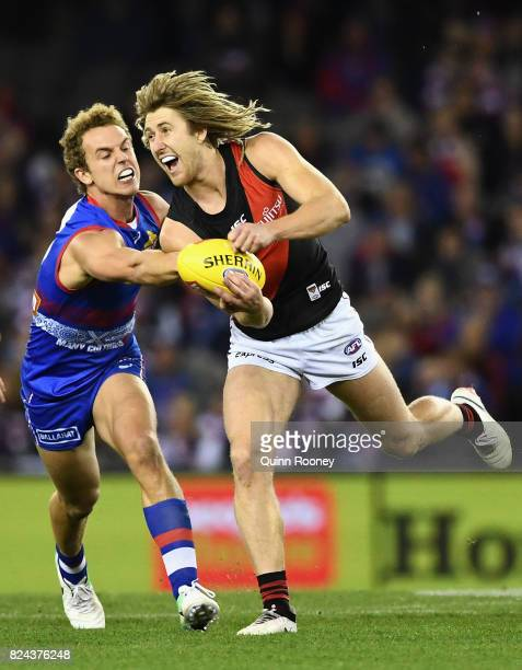 Dyson Heppell of the Bombers handballs whilst being tackled by Mitch Wallis of the Bulldogs during the round 19 AFL match between the Western...