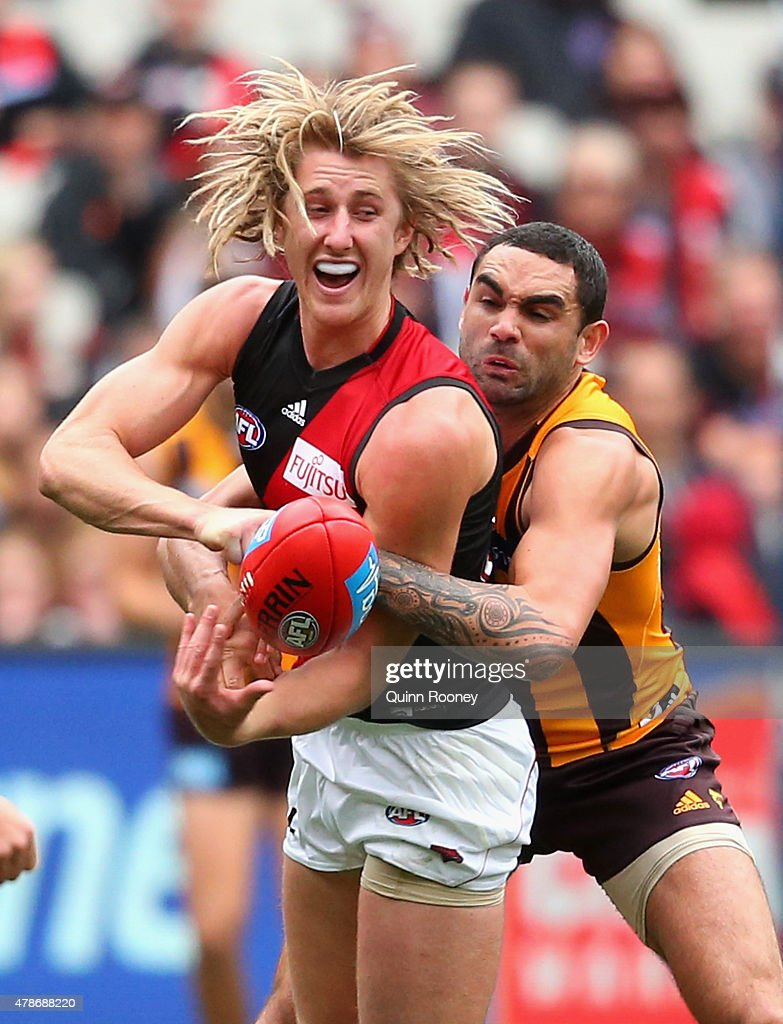 Dyson Heppell of the Bombers handballs whilst being tackled by Shaun Burgoyne of the Hawks during the round 13 AFL match between the Hawthorn Hawks and the Essendon Bombers at Melbourne Cricket Ground on June 27, 2015 in Melbourne, Australia.