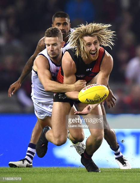 Dyson Heppell of the Bombers handballs whilst being tackled during the round nine AFL match between the Essendon Bombers and the Fremantle Dockers at...