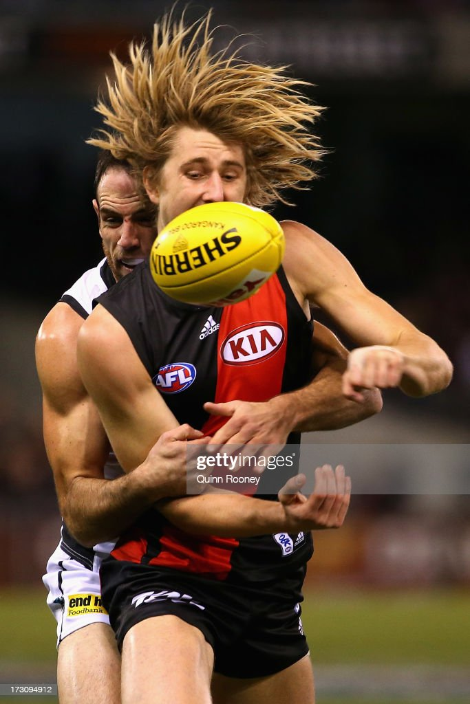 Dyson Heppell of the Bombers handballs whilst being tackled during the round 15 AFL match between the Essendon Bombers and Port Adelaide Power at Etihad Stadium on July 7, 2013 in Melbourne, Australia.