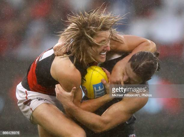 Dyson Heppell of the Bombers is tackled by Bryce Gibbs of the Blues during the 2017 AFL round 03 match between the Carlton Blues and the Essendon...