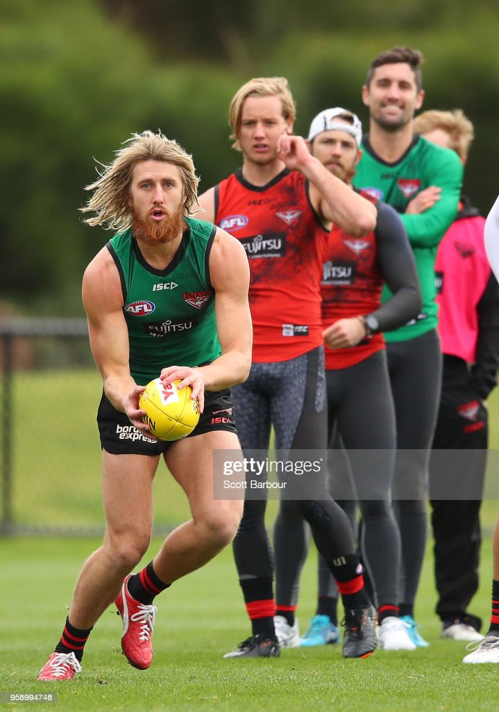 Dyson Heppell of the Bombers runs with the ball as his teammates look on during an Essendon Bombers AFL training session at The Hangar on May 16, 2018 in Melbourne, Australia.