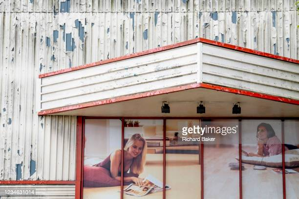 Dystopian lifestyle landscape showing beautiful women reclining on the floors of the aspirational homes, at the entrance of a retail park business in...