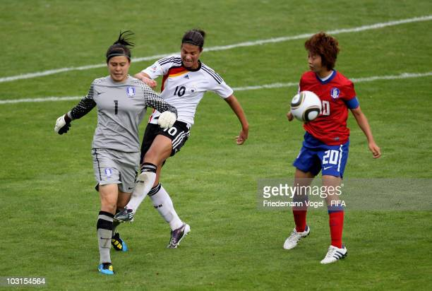 Dzsenifer Marozsan of Germany and Moon So Ri and Kim Hye Ri of South Korea battle for the ball during the FIFA U20 Women's World Cup Semi Final match...