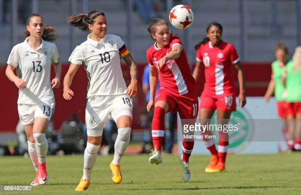 Dzsenifer Marozsan of Germany battles for the ball with Jessie Fleming of Canada during the women's international friendly match between Germany and...