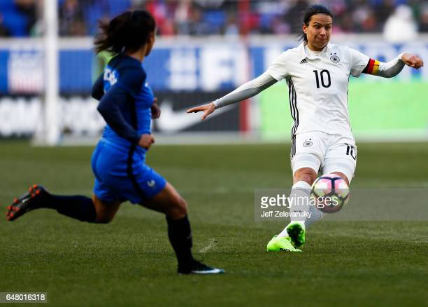 Dzsenifer Marozsán of Germany drives by Sakina Karchaoui of France during their match at Red Bull Arena on March 4 2017 in Harrison New Jersey