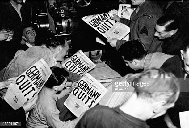 Eager soldiers pull copies of 'Stars and Stripes' from the press of the London Times at 9P M May 7 when an extra was put out to annouce the news of...