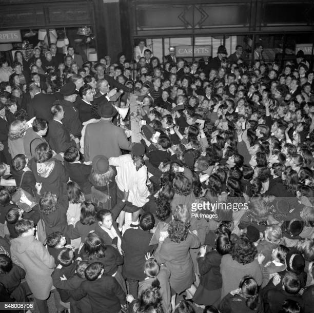 Eager young fans in a closepacked crowd thrust autograph books at singing star Cliff Richard at Woolwich He was switching on the borough's Christmas...