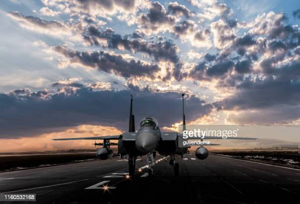 f-15 eagle jet fighter ready to takeoff on runway at sunset - military base stock pictures, royalty-free photos & images