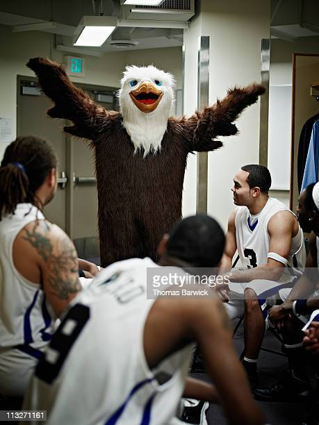 Eagle mascot with basketball team in locker room