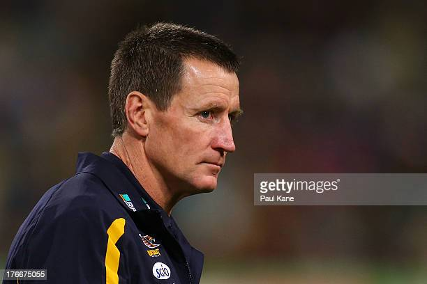 Eagles coach John Worsfold walks back to the coaches box after the three quarter time break during the round 21 AFL match between the West Coast...