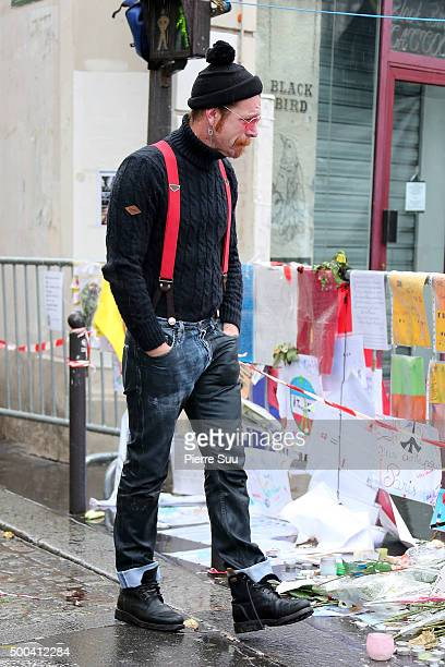 Eagles of Death Metal frontman Jesse Hughes shows his emotions as he looks at the flower memorial in front of The Bataclan concert hall on December...
