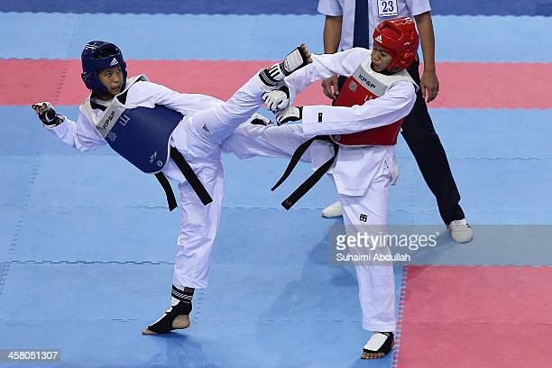 Eaimdra Aung of Myanmar fights Dwi Regina Ismail Uvaraj of Malaysia during the taekwondo women's 4649kg during the 2013 Southeast Asian Games at...
