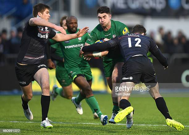 Eamonn Sheridan of London Irish is tackled by Duncan Taylor and Owen Farrell of Saracens during the Aviva Premiership match between Saracens and...