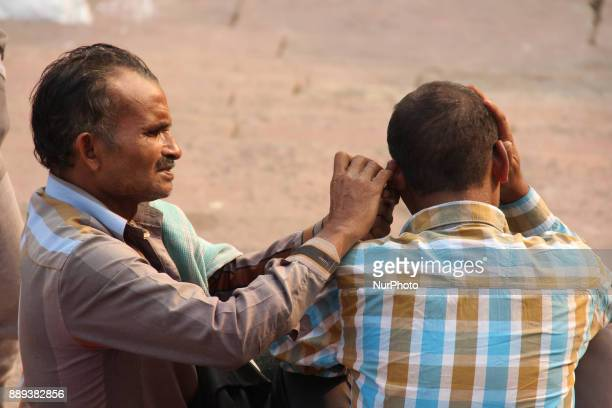 A ear cleaner cleans the ear of person on the steps of the biggest mosque of the city Jamia Masjid Old Delhi India on 10th December 2017