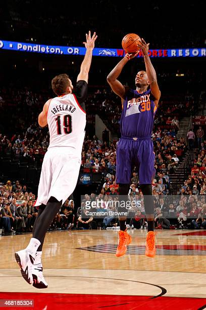 Earl Barron of the Phoenix Suns shoots against Joel Freeland of the Portland Trail Blazers during the game on March 30 2015 at Moda Center in...
