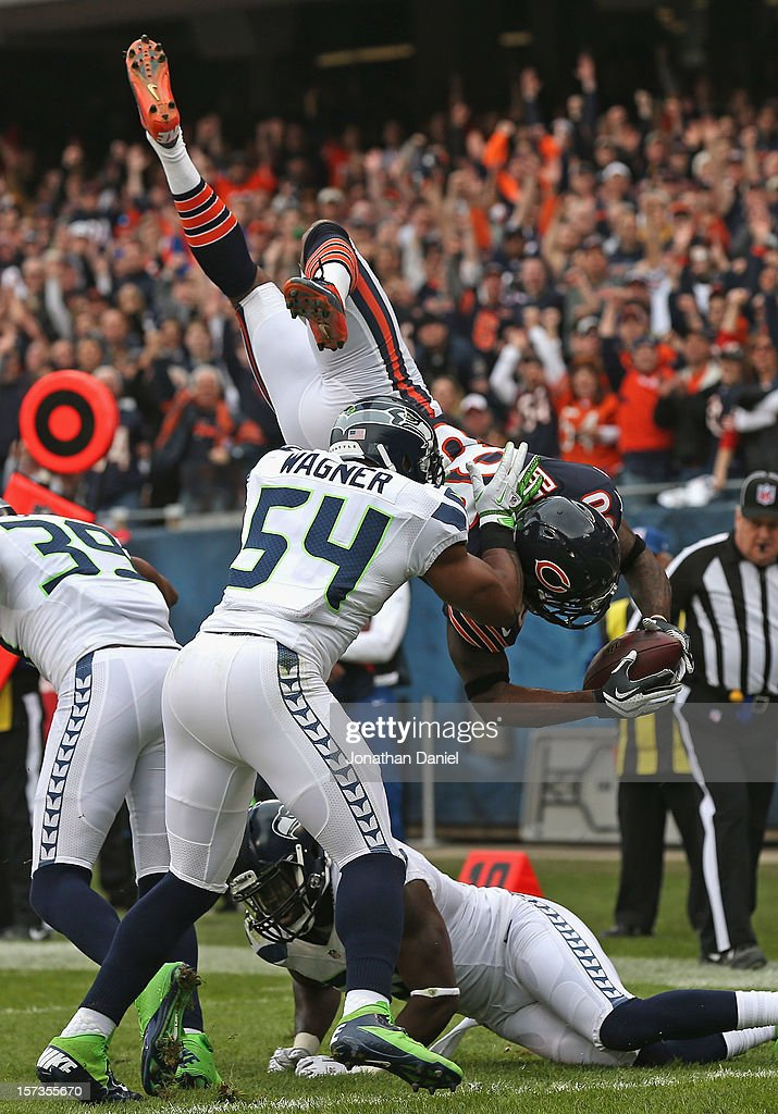 Earl Bennett #80 of the Chicago Bears flips over Bobby Wagner #54 and Kam Chancellor #31 of the Seattle Seahawks to score a touchdown at Soldier Field on December 2, 2012 in Chicago, Illinois.