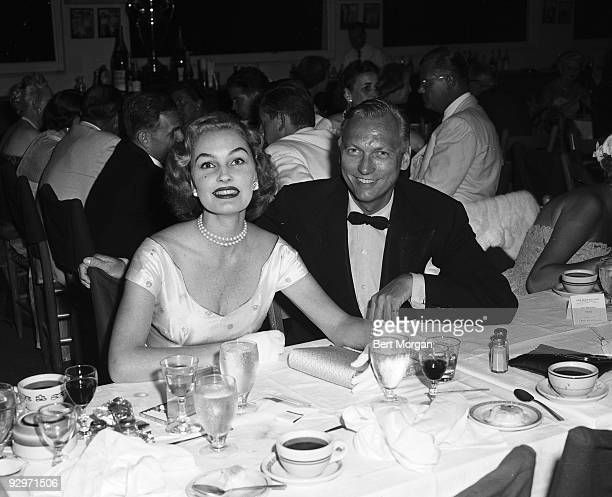 Earl Blackwell and Pamela Curran seated and smiling at a banquet at the Palm Beach Polo Club Palm Beach Florida c1955