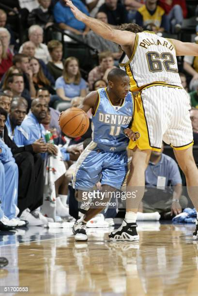 Earl Boykins of the Denver Nuggets dribbles around Scot Pollard of the Indiana Pacers during the preseason game at Conseco Fieldhouse on October 29,...