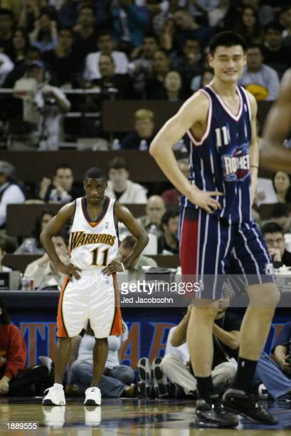 Earl Boykins of the Golden State Warriors and Yao Ming of the Houston Rockets rest during the game at The Arena in Oakland on March 21 2003 in...