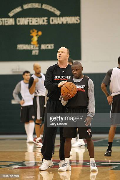 Earl Boykins of the Milwaukee Bucks holds the ball as head coach Scott Skiles explains a play during practice on October 19, 2010 at the Milwaukee...