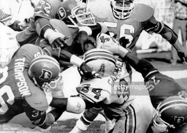 Earl Campbell of the Houston Oilers is tackled on the goalline by Rulon Jones Larry Evans Don Latimer Steve Foley and Billy Thompson of the Denver...