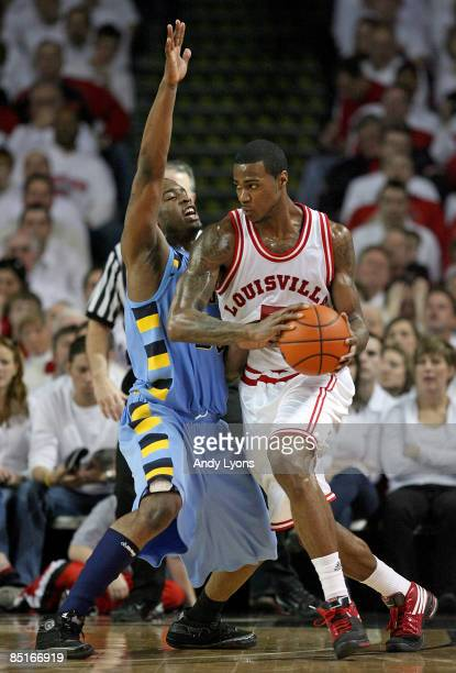 Earl Clark of the Louisville Cardinals dribbles the ball while defended by Wesley Matthews of the Marquette Golden Eagles during the Big East...