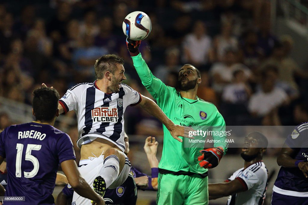Earl Edwards Jr of Orlando City saves from Gareth McAuley of West Bromwich Albion during the pre-season friendly between Orlando City and West Bromwich Albion at Orlando Citrus Bowl on July 15, 2015 in Orlando, Florida.