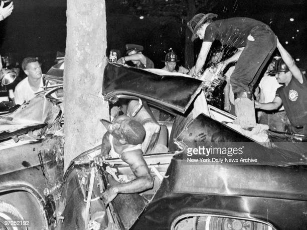 Earl Hyman grimaces in pain as firemen try to free him and other youths trapped inside a stolen car which crashed into a tree at 176th St and Grand...