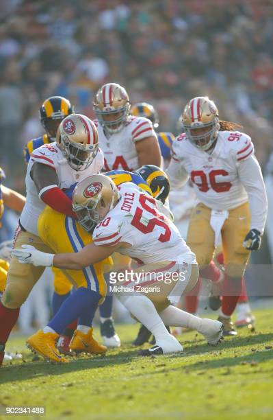 Earl Mitchell and Brock Coyle of the San Francisco 49ers tackle Malcolm Brown of the Los Angeles Rams during the game at Los Angeles Memorial...