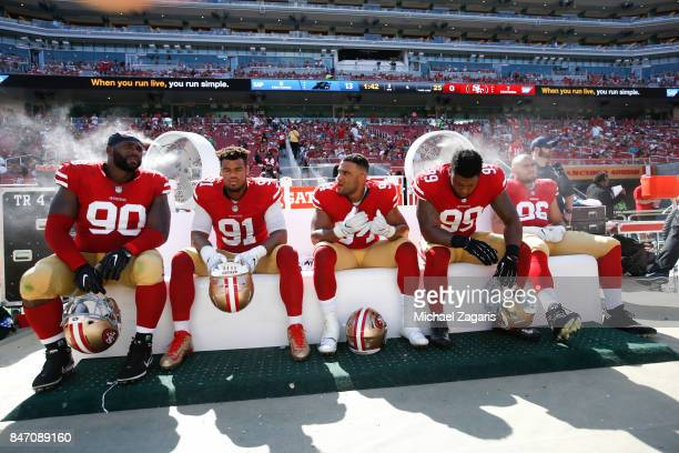 Earl Mitchell Arik Armstead Solomon Thomas and DeForest Buckner of the San Francisco 49ers sit on the bench during the game against the Carolina...