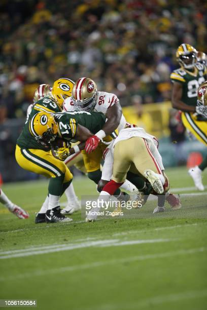 Earl Mitchell of the San Francisco 49ers tackles Davante Adams of the Green Bay Packers during the game at Lambeau Field on October 15 2018 in Green...