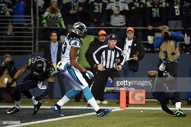 Earl Thomas of the Seattle Seahawks attemps to intercept a pass intended for Kelvin Benjamin of the Carolina Panthers thrown by Cam Newton that was...