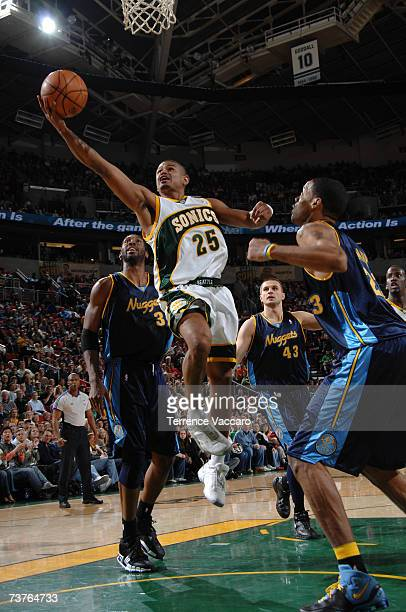 Earl Watson of the Seattle SuperSonics goes to the basket between the defense of Nene Linas Kleiza and Marcus Camby of the Denver Nuggets on APRIL 1...
