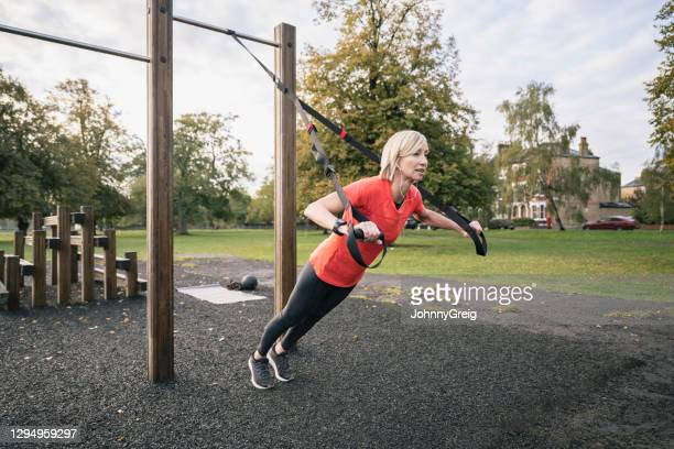 early 50s sportswoman doing suspension training chest press - clapham common stock pictures, royalty-free photos & images